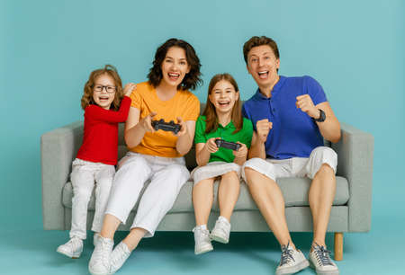 Happy family together. Mother, father and their children girls playing video games. People having fun on bright blue background.