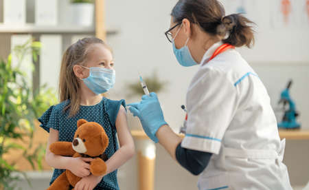 Doctor vaccinating child at hospital.