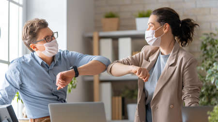 Businessman and businesswoman with medical mask working in office. Covid-19 time.
