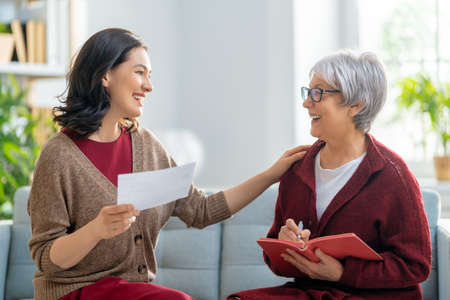 Two women, sitting on the sofa with a paper receipt, are calculating expenses, managing the family budget.