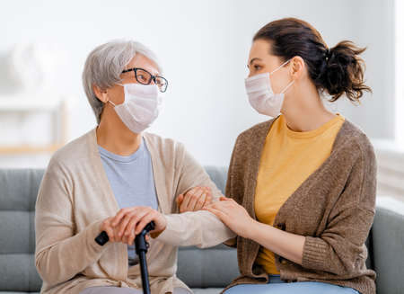 Adult daughter and senior parent wearing facemasks during flu outbreak. Help for the convalescent.