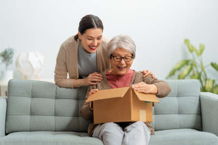 Two women are holding cardboard box sitting on sofa at home.