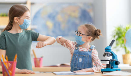 Back to school! Cute industrious children are sitting at desks indoors. Kids are wearing facemasks learning in class. Stock Photo