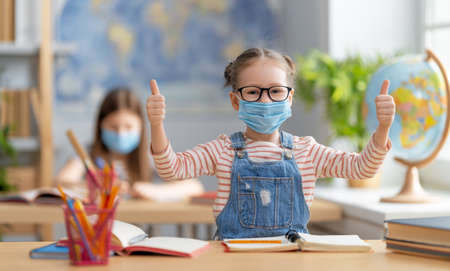 Back to school! Cute industrious children are sitting at desks indoors. Kids are wearing facemasks learning in class.