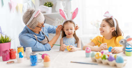 A grandmother and her granddaughters painting eggs. Happy family preparing for Easter. Cute little children girls wearing bunny ears.