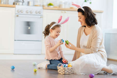 Happy holiday! A mother and her daughter with painting eggs. Family preparing for Easter. Cute little child girl is wearing bunny ears.