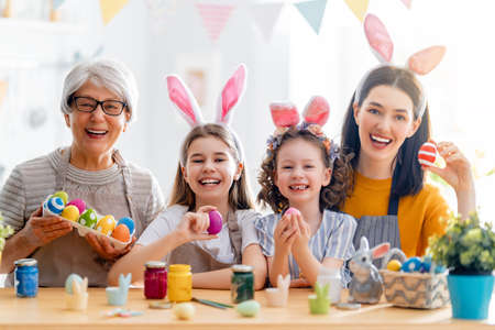 Mother, grandma and children are painting eggs. Happy family are preparing for Easter. Cute little girls wearing bunny ears. Foto de archivo