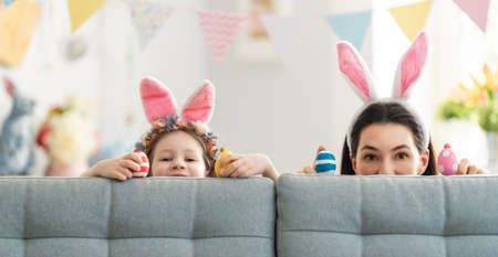 Happy holiday! Mother and her daughter with painting eggs. Family celebrating Easter. Cute little child girl is wearing bunny ears. Foto de archivo
