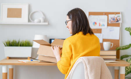 Beautiful young woman is holding cardboard box sitting at desk at home office. Foto de archivo