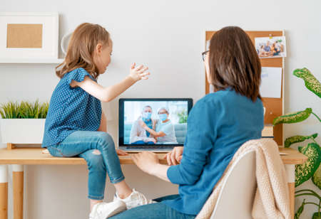 Woman and child are using pc for remote talking with parents during coronavirus and flu outbreak. Virus and illness protection, home quarantine. COVID-2019.