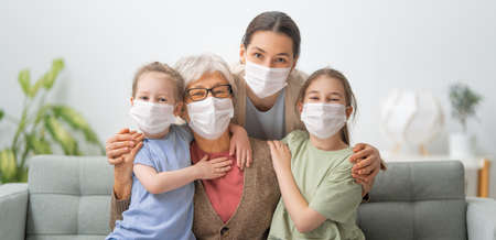 A nice girls, her mother and grandmother enjoying spending time together at home. People wearing face masks.