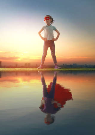 Little child playing superhero and looking at her reflection in water surface. Kid on the background of sunset sky. Girl power concept