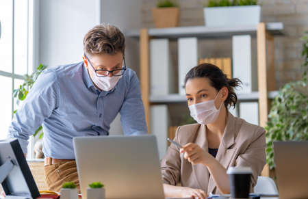 Businessman and businesswoman with medical mask working in office. Covid-19 time. Foto de archivo