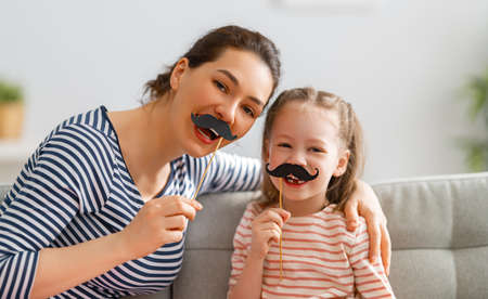 Mom and her child daughter are playing at home. Cute girl are holding paper mustache on stick. Family holiday and togetherness.