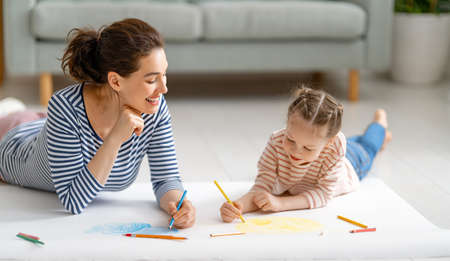 Happy family. Mother and daughter drawing together. Adult woman spending time with child girl.