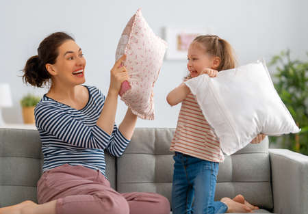 Happy loving family. The mother and her child girl are fighting pillows. Foto de archivo