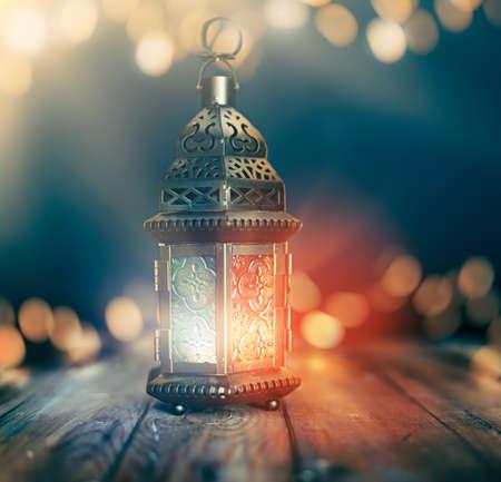 Ornamental Arabic lantern with burning candle glowing at night. Festive greeting card, invitation for Muslim holy month Ramadan Kareem. Foto de archivo