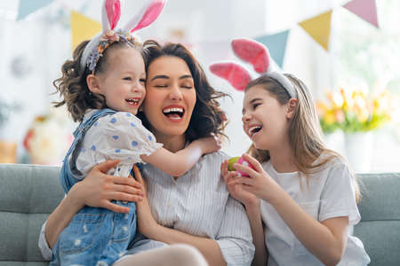 Happy holiday! Mother and her daughters with painting eggs. Family celebrating Easter. Cute little children girls are wearing bunny ears.