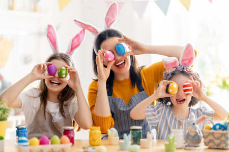 Happy holiday! A mother and her daughters are painting eggs. Family preparing for Easter. Cute little children girls are wearing bunny ears. Foto de archivo