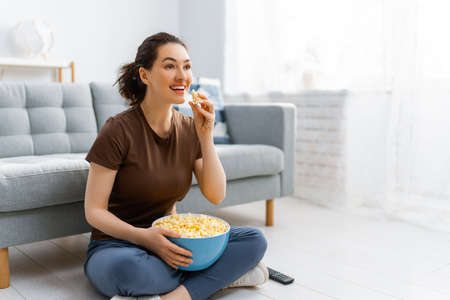 Young woman watching  TV, movies with popcorn. Girl spending time at home.