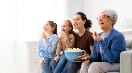 Happy family watching TV, movies with popcorn at home. Mother, daughters and grandmother spending time together.