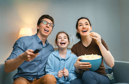 Happy family watching projector, TV, movies with popcorn in the evening at home. Mother, father and daughter spending time together. Foto de archivo