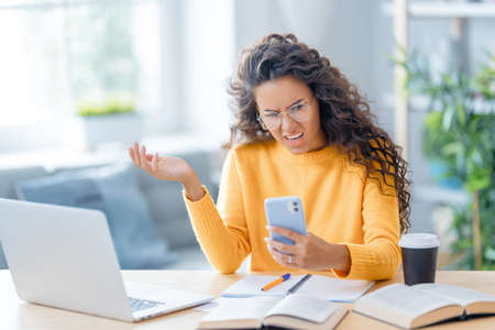 Confused frustrated young businesswoman studying online, watching webinar, podcast on laptop, making notes, sitting at work desk. E-learning concept. Imagens