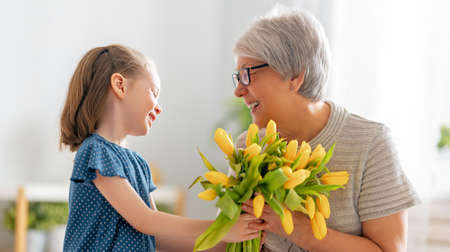 Happy mother's day. Child is congratulating granny giving her flowers. Grandma and girl smiling and hugging. Family holiday and togetherness.