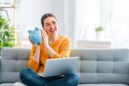 Happy woman is calculating expenses, managing the family budget.