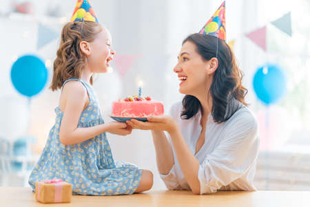 The kid is blowing out the candles on the cake. Mother and daughter are celebrating birthday.