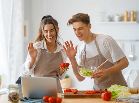 Healthy food at home. Happy loving couple is preparing the proper meal in the kitchen. 免版税图像