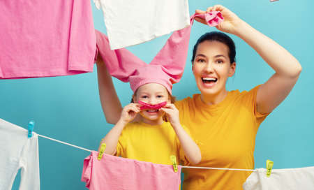 Beautiful young woman and child girl little helper are having fun and smiling while doing laundry and drying.