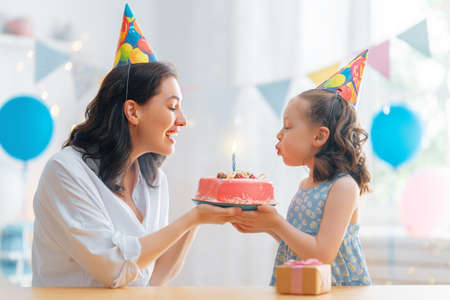 The kid is blowing out the candles on the cake. Mother and daughter are celebrating birthday. 免版税图像
