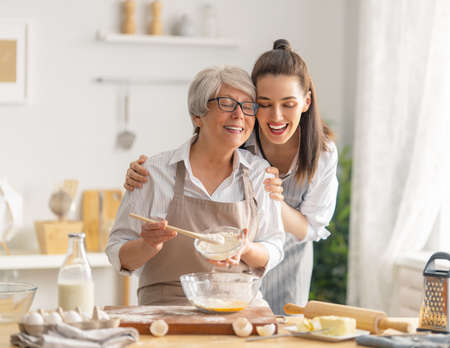 Happy family in the kitchen. Mother and her adult daughter are preparing pastry. 免版税图像
