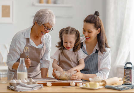 Happy loving family are preparing bakery together. Granny, mom and child are cooking cookies and having fun in the kitchen. Homemade food and little helper. 免版税图像