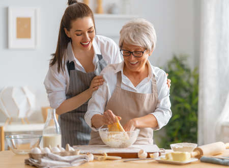 Happy family in the kitchen. Mother and her adult daughter are preparing pastry. Archivio Fotografico