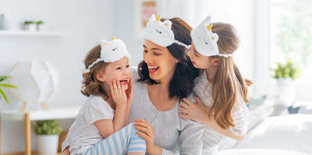 Nice girls and their mother are enjoying sunny morning. Good time at home. Children waking up from sleep. Family playing on the bed in the bedroom. 免版税图像
