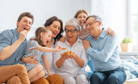 Nice girls, their mother, father, grandfather and grandmother are enjoying spending time together at home. Family time.