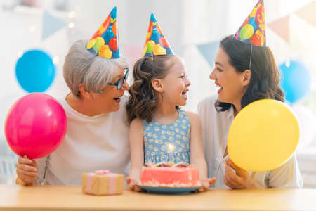 The kid is blowing out the candles on the cake. Grandmother, mother and daughter are celebrating birthday. 免版税图像