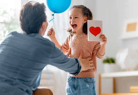 Child daughter is congratulating her father and giving him postcard. Dad and girl are smiling and hugging. Family holiday and togetherness.