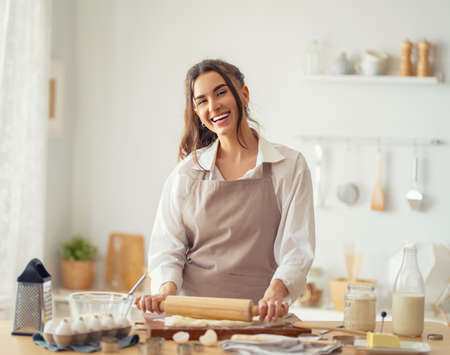 Happy woman is preparing bakery. Girl is cooking cookies in the kitchen. Homemade food.
