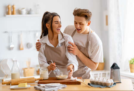 Happy loving couple is preparing the pastry in the kitchen. 免版税图像