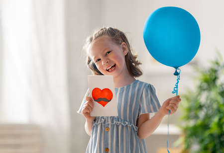 Happy child with air balloon and postcard for her father.