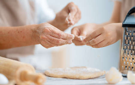 Close up view of bakers are working. Homemade bread. Hands preparing dough on wooden table.
