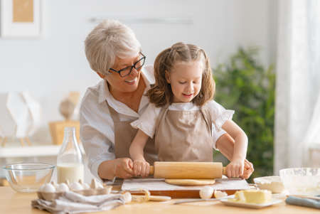 Happy loving family are preparing bakery together. Granny and child are cooking cookies and having fun in the kitchen.