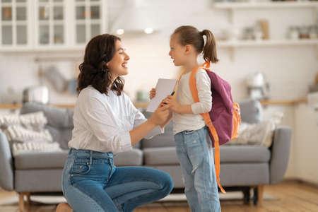 Happy family preparing for school. Little girl with mother. Standard-Bild
