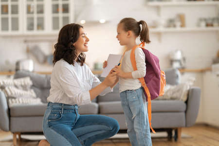Happy family preparing for school. Little girl with mother. Stock Photo