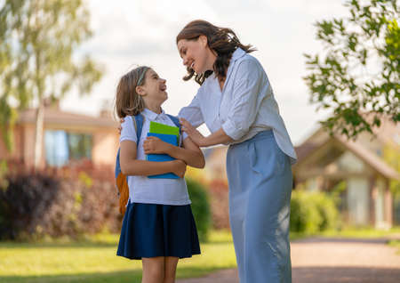 Parent and pupil of primary school going hand in hand. Woman and girl with backpack behind the back. Beginning of lessons. Reklamní fotografie