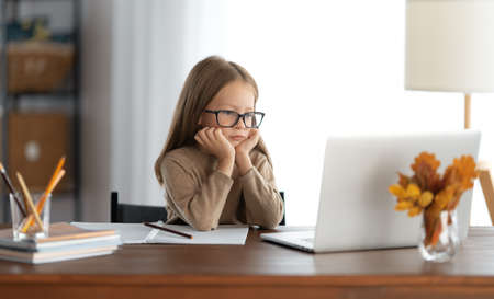 Back to school. Thinking child is sitting at desk. Girl doing homework or online education.