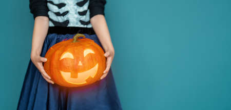 Happy Halloween! Cute little laughing girl in pirate costume on blue wall background.